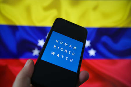 Viersen, Germany - July 9, 2020: View on smartphone screen with logo lettering of human rights watch organization. Blurred Venezuela flag background. (Focus on human) Redactioneel