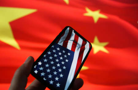 Chinese american economic relationship concept: View on hand holding mobile phone with USA flag. Blurred flag of China background. (selective focus on stars in upper row) Redactioneel