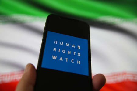 Viersen, Germany - July 9, 2020: View on smartphone screen with logo lettering of human rights watch organization. Blurred Iran flag background. (Focus on human)