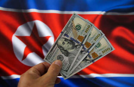 Viersen, Germany - July 9, 2020: View on isolated hand with 100 dollar bills. Blurred North Korea flag background. (focus on head)