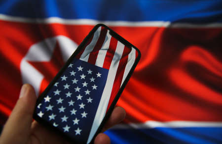 Viersen, Germany - July 9, 2020: View on hand holding mobile phone with USA flag. Flag of North Korea background. (focus on upper part of american flag) Redactioneel