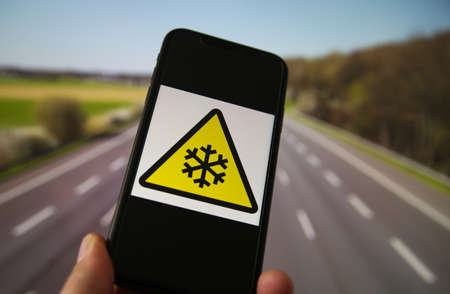 View on hand holding mobile phone with yellow triangle international low temperature hazard symbol. Blurred highway background. Redactioneel