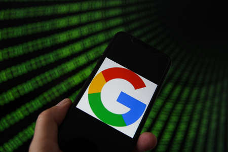 Viersen, Germany - July 9, 2020: View on mobile phone with google logo hold by hand. Screen with tunnel of binary code numbers background. (Selective focus on logo)