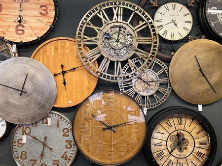 Venlo, Netherlands - July 9, 2020: View on group of various isolated round vintage clocks on wall