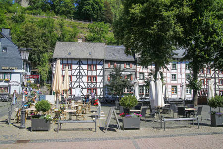 Monschau, Germany (Eifel) - July 9, 2020: View on square with timber frame monument houses and trees in center of medieval village