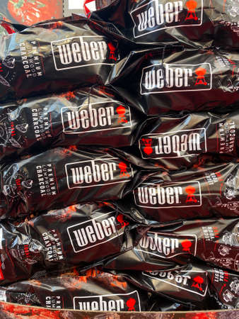Venlo, Netherlands - July 9, 2020: View on isolated stack Weber grill barbecue charcoal bags in supermarket