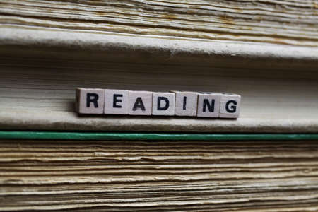 Closeup of isolated antique old book pile text blocks and yellowed pages with wooden alphabet cubes forming word literature