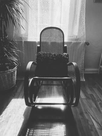 View on empty rocking chair in living room with shadow from backlight of window - grieve and loss of loved person concept