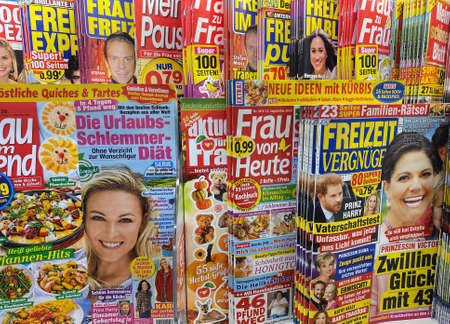 Viersen, Germany - August 17. 2020: View on isolated kiosk shelf with variety of german yellow gossip press magazines