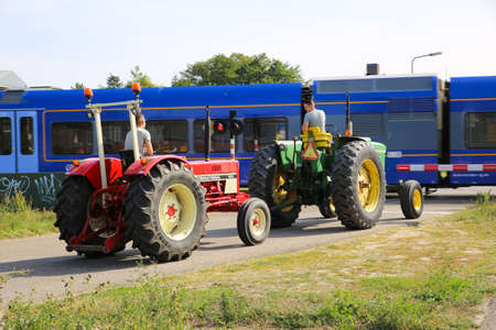 Swalmen, Netherlands - September 20, 2020: View on two vintage tractors waiting at closed railway crossing barriers