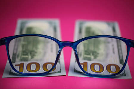 View through isolated blue eye glasses on hundred dollar paper banknote with pink background