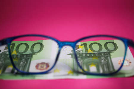 View through isolated blue eye glasses on hundred euro paper banknote with pink background 写真素材