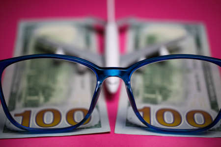 View on isolated eyeglasses with blurred plane and two hundred dollar paper banknotes on pink backgound (focus on center of eyeglass frame)