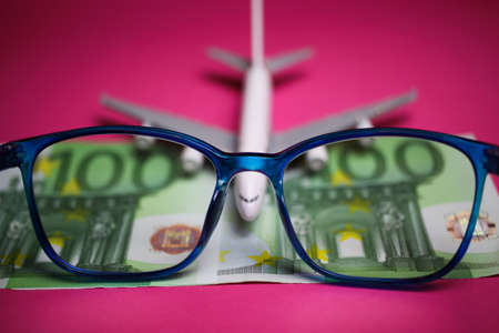 View on isolated eyeglasses with blurred plane and two hundred euro paper banknotes on pink backgound (focus on center of eyeglass frame)