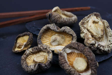 Macro closeup of isolated dried chinese shiitake mushrooms on slate stone background (focus on central mushroom)