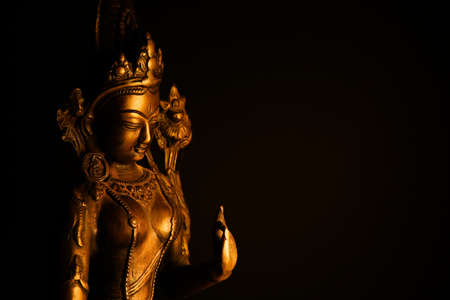 Close up of isolated illuminated hindu Shiva god golden bronze statue with raised hand on blank black background