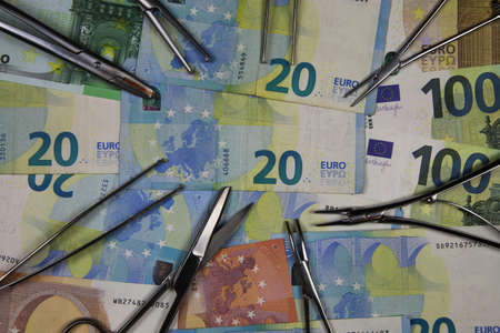 View on surgical instruments on euro paper money currency banknotes - financial market regulation concept 스톡 콘텐츠