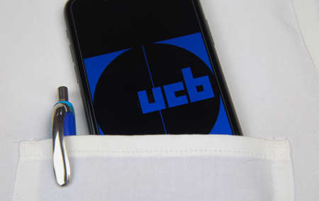 Viersen, Germany - April 9. 2020: Close up of mobile phone screen with logo lettering of UCB pharmaceutical company in pocket of white doctors coat with pencil