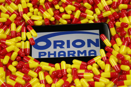 Viersen, Germany - April 9. 2020: Close up of mobile phone screen with logo lettering of finnish orion pharma oyj pharmaceutical company on pile yellow red drug capsules (focus on center of lettering) Publikacyjne