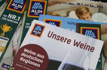 Viersen, Germany - January 13. 2021: Closeup of weekly printed advertising inserts from german Aldi discounter with focus on catalog with german wine selection