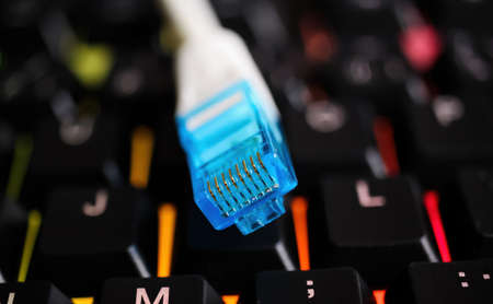 Macro closeup of isolated blue white network connector cable on illuminated computer keyboard