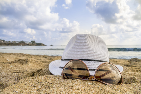bowler: bowler hat with sunglasses on the beach