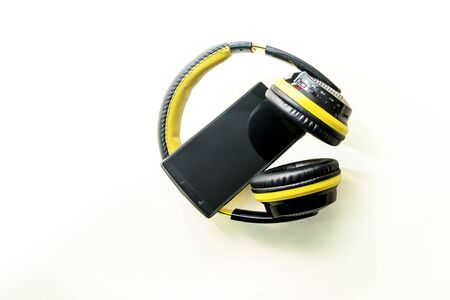 Black and yellow headphones and black mobile phone Stock Photo