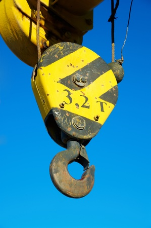 Hook of the elevating crane against the blue sky Stock Photo - 8785940