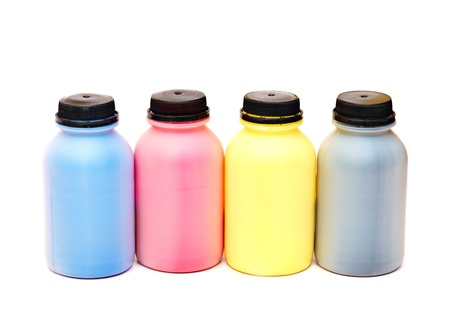 Four color bottles of a paint with black stoppers.