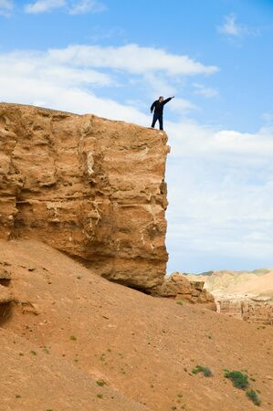 Man on a rock with the lifted hand photo