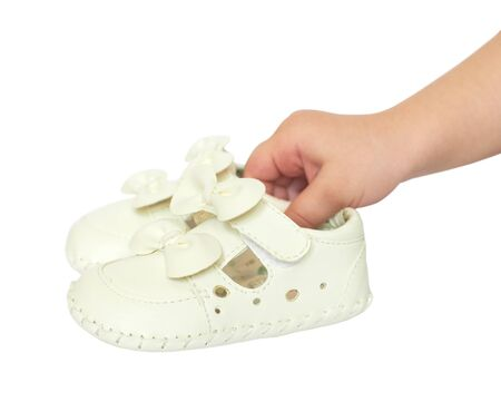 Kids  hand holds small white baby shoes, studio shoot isolated on white  photo