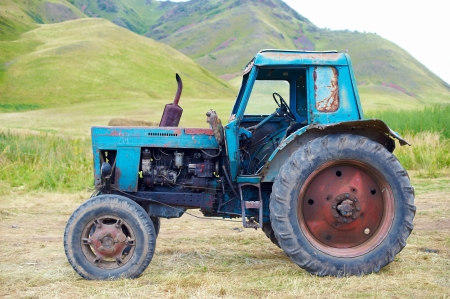 Old rusty tractor on grass photo