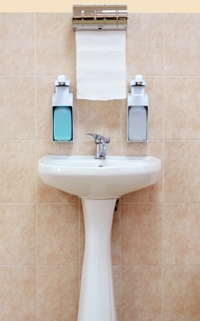 Washbasin with a paper towel and liquid soap on the background wall of brown tiles photo