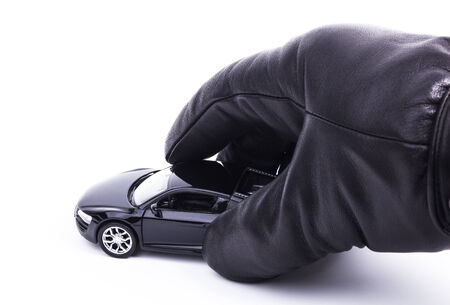 A gloved hand is picking up a sports car Stock Photo