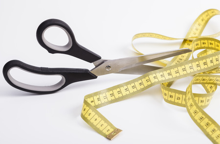 A scissors is cutting a tape measure Stock Photo - 26811833
