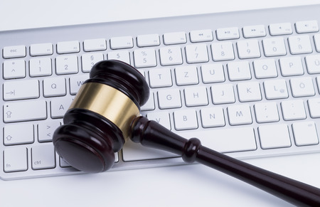 computer law: Close up of wooden gavel at the computer keyboard