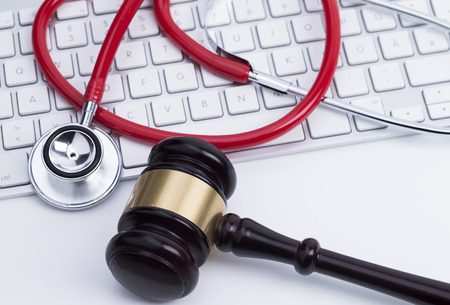 Close up of wooden gavel and a stethoscope at the computer keyboard
