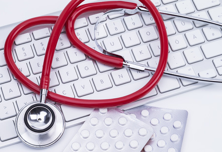 Image shows a red stethoscope at a computer keyboard photo