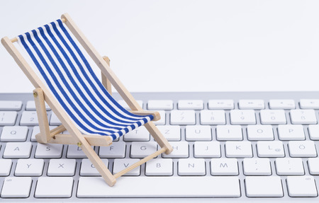 Image shows a deck chair on a keyboard, isolated on white background photo