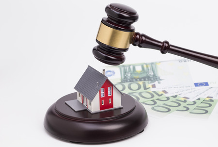 Wooden judge gavel with house and money isolated on white background photo