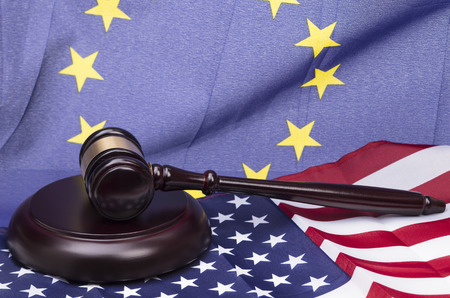 u.s. flag: Image shows a wooden in front of a european and u s a flag Stock Photo