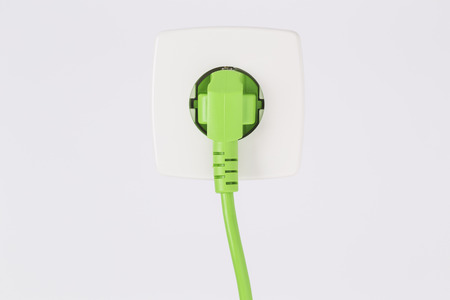 Green power plug into power outlet against a white background Standard-Bild
