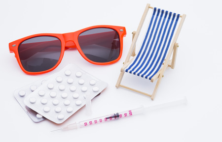 Image shows a deckchair sunglasses pills and a injection