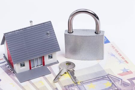 minature: Image shows a minature house with closed padlock on some of Euro Banknotes