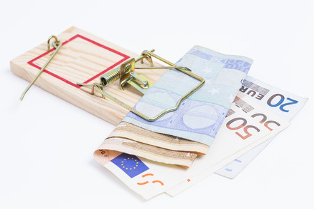 entrapment: Image shows a mousetrap with some banknotes on white background Stock Photo