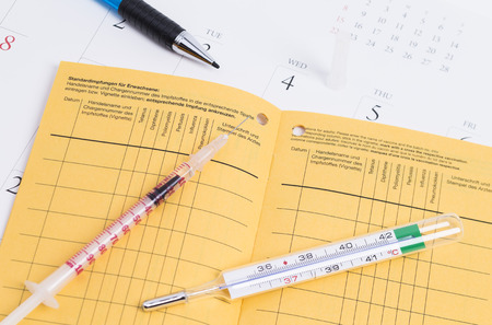 inoculate: Certificate of Vaccination with a injection and pen on calender Stock Photo