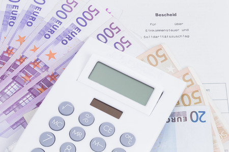 wage earners: Image shows a tax assessment with money and calculator Stock Photo