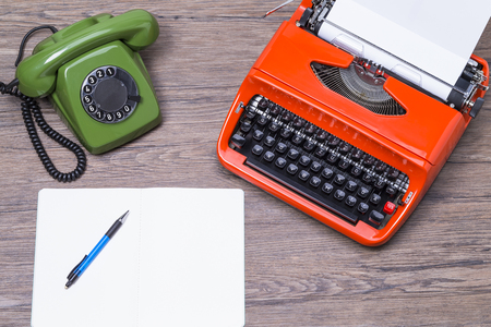 maquina de escribir: Retro teléfono y máquina de escribir sobre una mesa de madera con Top View Foto de archivo