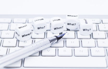 Images shows diferent question dices with pen on a compter keyboard
