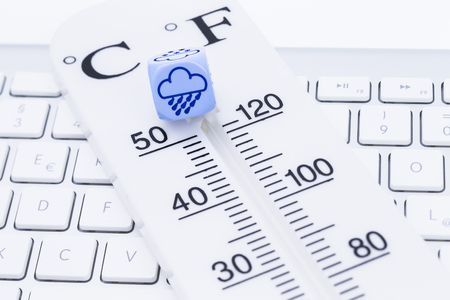 termómetro: La imagen muestra un termómetro con el cubo en un teclado Foto de archivo